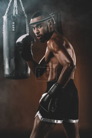 Photo for Side view of confident muay thai fighter with punching bag behind - Royalty Free Image