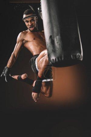 Photo pour En colère muay thaï combattant formation avec sac de boxe, concept sport action - image libre de droit