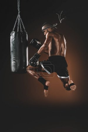Photo for Side view of muay thai fighter training with punching bag, action sport concept - Royalty Free Image