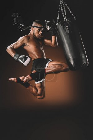 Photo for Side view of concentrated muay thai fighter training with punching bag, action sport concept - Royalty Free Image