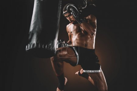 Photo for Focused muay thai fighter training with punching bag, action sport concept - Royalty Free Image