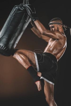 Photo pour Vue latérale du muay thai fighter formation avec sac de boxe, concept sport action - image libre de droit