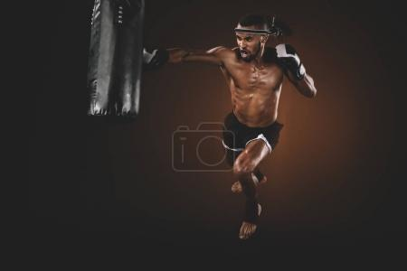 Photo pour Combattant thaï muay en colère pratiquant coup de poing sur le sac de boxe, concept sport action - image libre de droit
