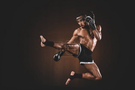 Photo for Side view of angry trainign muay thai fighter in boxing gloves, action sport concept - Royalty Free Image