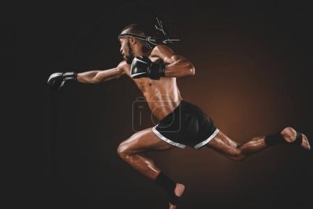 Photo for Side view of muay thai fighter in boxing gloves practicing punch, action sport concept - Royalty Free Image