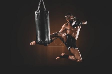 Photo for Side view of focused muay thai fighter practicing kick on punching bag, action sport concept - Royalty Free Image