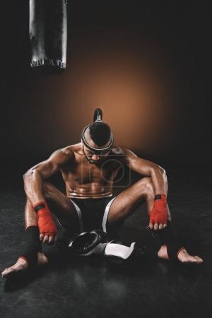Photo for Tired muay thai fighter with mongkhon on head sitting on floor - Royalty Free Image