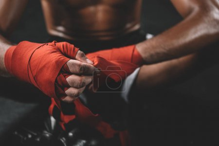 Photo for Partial view of muay thai fighter swathign hand in boxing bandage - Royalty Free Image