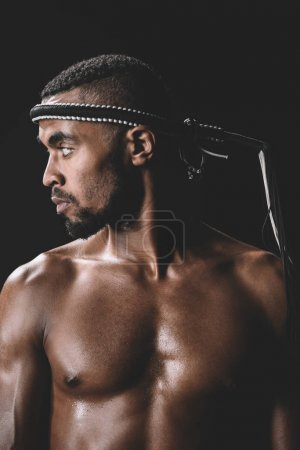Photo for Side view of confident muay thai fighter with mongkhon on head isolated on black - Royalty Free Image