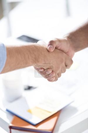 Foto de Vista superior de los hombres de negocios estrechando las manos por encima de la mesa con papeles, concepto de trabajo en equipo de negocios - Imagen libre de derechos