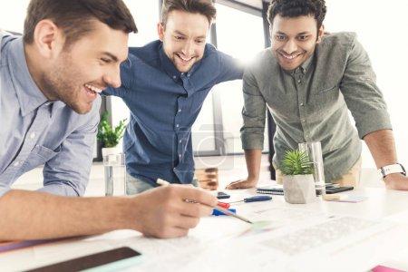 Photo pour Trois jeunes hommes d'affaires penchés à table et travaillant ensemble au projet, concept de travail d'équipe - image libre de droit