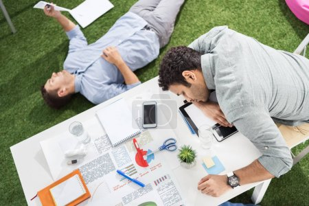 Businessmen sleeping at modern office