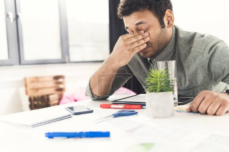 Photo pour Jeune homme d'affaires occasionnel fatigué assis à la table au bureau, établissement d'affaires - image libre de droit