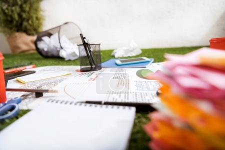 Photo for Heap of business objects and office supplies laying on green grass carpet at office, business establishment - Royalty Free Image