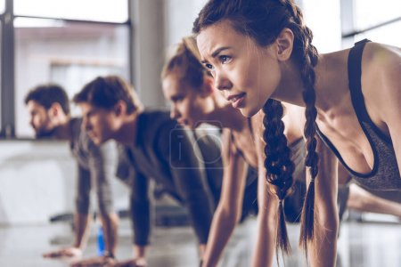 Photo for Athletic young people in sportswear doing push ups or plank at the gym, group fitness concept - Royalty Free Image
