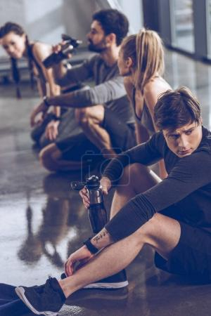 sporty people resting in gym