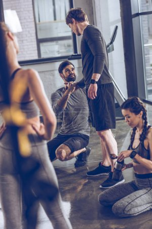 Photo for Group of athletic young people in sportswear sitting on floor and resting at the gym, group fitness concept - Royalty Free Image
