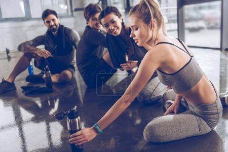 Photo pour Groupe de jeunes sportifs en vêtements de sport assis sur le sol et se reposant à la salle de gym, concept de fitness de groupe - image libre de droit