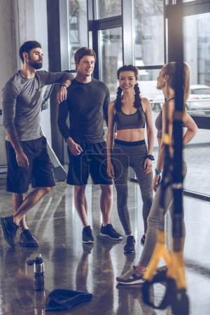 Photo for Group of athletic young people in sportswear standing and resting at the gym, group fitness concept - Royalty Free Image
