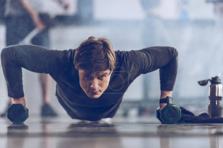 Photo for Athletic young sportsman doing push ups with dumbbells at the gym, gym workout concept - Royalty Free Image