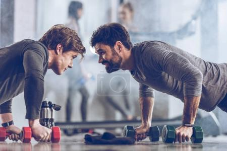 Photo for Athletic young sportsmen doing push ups with dumbbells at the gym, gym workout concept - Royalty Free Image