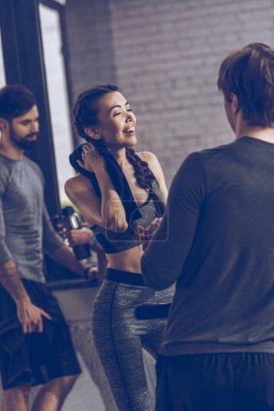 Foto de Jóvenes atléticos hablando en ropa deportiva en el gimnasio, el concepto de grupo de fitness - Imagen libre de derechos