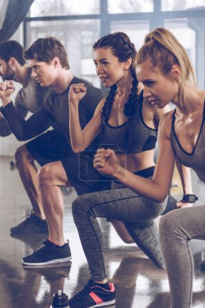 Photo for Group of athletic young people in sportswear doing lunge exercise at the gym, aerobic fitness concept - Royalty Free Image