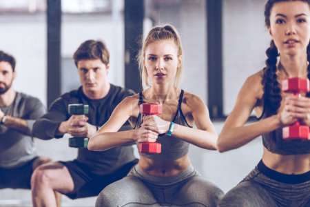 Photo for Group of athletic young people in sportswear with dumbbells squatting and exercising at the gym - Royalty Free Image
