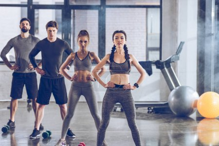 Photo for Group of athletic young people in sportswear exercising at the gym - Royalty Free Image