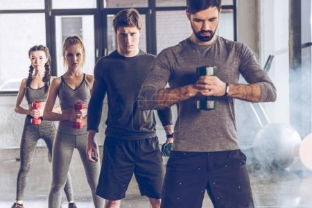 Photo for Group of athletic young people in sportswear with dumbbells exercising at the gym - Royalty Free Image