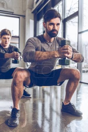 Photo for Muscular young men in sportswear with dumbbells exercising at the gym - Royalty Free Image