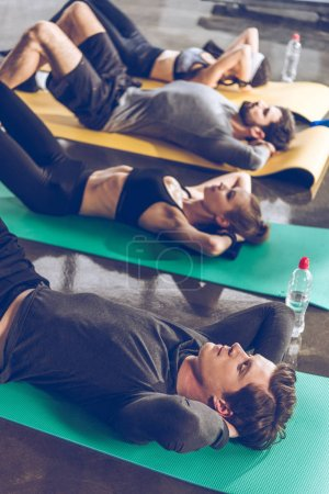 Photo for Sporty young people doing abs on yoga mats while exercising at the gym - Royalty Free Image