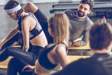 Photo for Smiling young sporty people lying on yoga mats and talking while exercising at the gym - Royalty Free Image