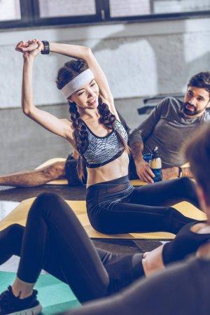 Photo pour Jeunes sportifs se reposant et s'étirant sur des tapis de yoga tout en faisant de l'exercice à la salle de gym - image libre de droit