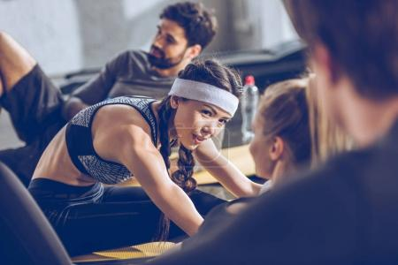 Photo for Sporty young people lying on yoga mats and exercising at the gym - Royalty Free Image