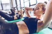 Athletic young people exercising in gym