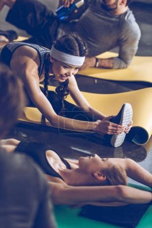 Photo pour Jeunes sportifs allongés sur des tapis de yoga et faisant de l'exercice au gymnase - image libre de droit