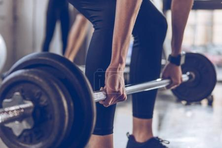 Photo for Close-up partial view of sportswoman lifting barbell at gym workout - Royalty Free Image