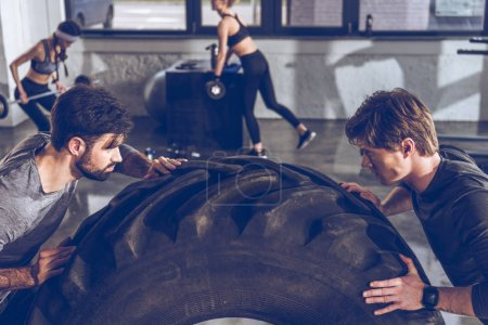 Photo for Young sportsmen exercising with big tire at gym workout - Royalty Free Image