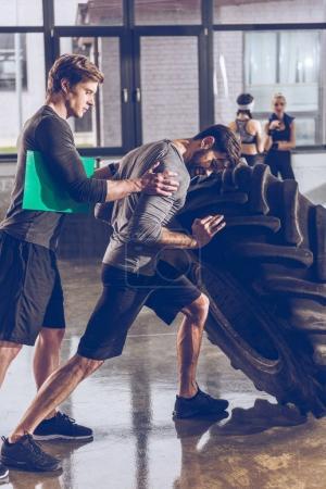 Foto de Vista lateral del entrenador ayudando a hombre empuja neumático mientras se ejercita en el gimnasio - Imagen libre de derechos