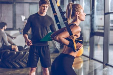 Photo for Side view of sportive woman exercising with trx gym equipment with trainer near by - Royalty Free Image