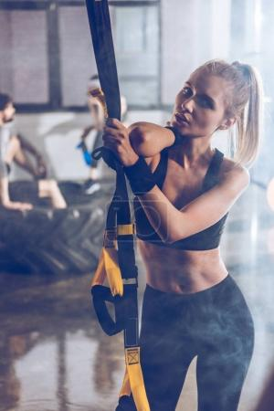 Photo for Portrait of serious sportive woman holding trx gym equipment - Royalty Free Image