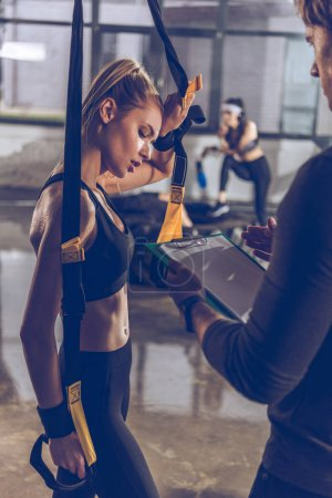 Photo for Side view of man helping sportive woman exercising with trx gym equipment - Royalty Free Image