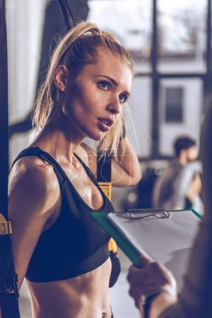 Foto de Retrato de mujer cansada deportiva con gimnasio trx - Imagen libre de derechos