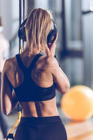 Photo for Back view of woman listening music in headphones near trx equipment in gym - Royalty Free Image