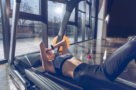 Photo for Side view of tired sportive woman lying on treadmill in gym - Royalty Free Image