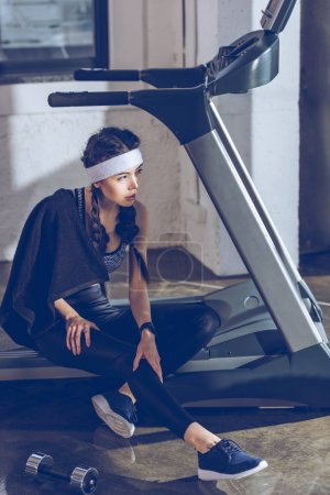 Photo for Side view of tired sportive woman sitting on treadmill in gym - Royalty Free Image