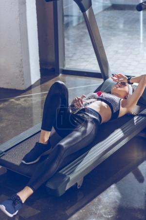 Foto de Vista lateral de cansada mujer deportiva caminadora en el gimnasio de mentira - Imagen libre de derechos
