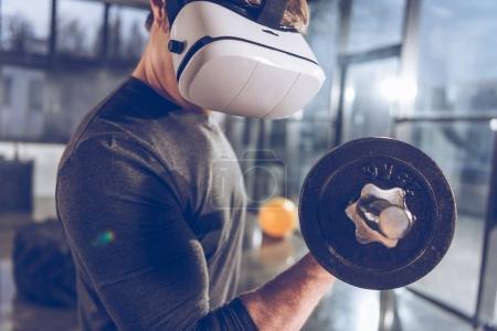 Photo pour Vue latérale de l'homme dans l'exercice de casque de réalité virtuelle avec l'haltère dans la salle de gym - image libre de droit