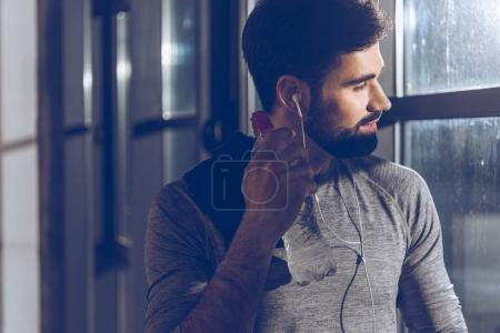 man listening music in earphones